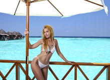 Young pretty woman stands in bathing suit on platform at villa on water, Maldives Stock Photo