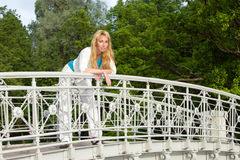 Young pretty woman stands on a bridge Royalty Free Stock Images