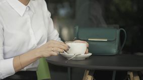 Young pretty woman in street cafe with cup stock footage