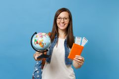 Young pretty woman student in glasses with backpack holding world glove, passport, boarding pass tickets isolated on. Blue background. Education in university stock photography