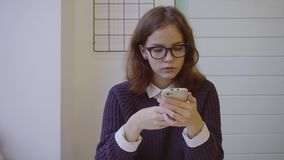 Young pretty woman student texting on her smart phone in the cafe. 4K stock video footage