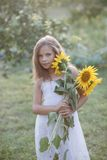 Young pretty woman on a sunflowers Stock Photos