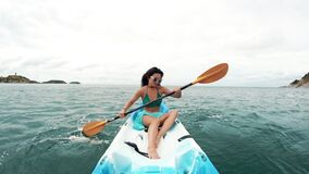 Young pretty woman in sunglasses rowing in a kayak. Tourism and recreation in Thailand. Charming cute Asian woman travel