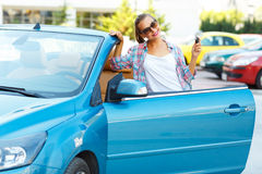 Young pretty woman in sunglasses standing near convertible with Stock Image