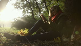 Young pretty woman in sunglasses with tablet computer in beautiful autumn park. stock footage
