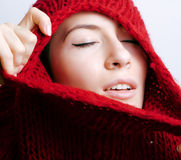 Young pretty woman in sweater and scarf all over her face, winter cold close up coming, red lips makeup Stock Photo