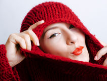 Young pretty woman in sweater and scarf all over her face, winter cold close up coming, red lips makeup Royalty Free Stock Photo