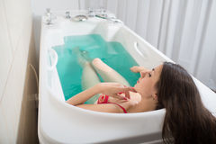 Young pretty woman takes mineral baths. At the medical center royalty free stock photo