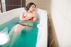 Young pretty woman takes mineral baths. At the medical center stock images