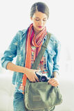 Young pretty woman taking camera from her bag Royalty Free Stock Images