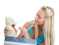 Young pretty woman taking out teddy bear from shop bag. Isolated on white stock images