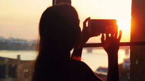 Young pretty woman taking photos of city with blurred architectures on mobile smart phone at home window during sunset. Young woman taking photos of city with Royalty Free Stock Photos