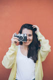 Young pretty woman taking picture with old camera Stock Photo