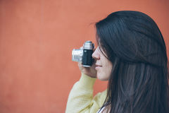Young pretty woman taking picture with old camera Royalty Free Stock Images