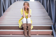Young pretty woman talking at cellular phone on  Bridge - woman having a conversation at smartphone Royalty Free Stock Image