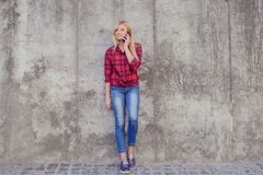 Young pretty woman talking on mobile phone while having a walk i royalty free stock photography