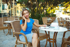 Young pretty woman talking on the phone and makes notes in a not Stock Photos