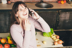 Young and pretty woman talks on a mobile phone in the kitchen while preparing dinner while standing in the kitchen. Check the recipe. Young and pretty woman Royalty Free Stock Photo