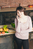 Young and pretty woman talks on a mobile phone in the kitchen while preparing dinner while standing in the kitchen. Check the recipe. Young and pretty woman Stock Photo