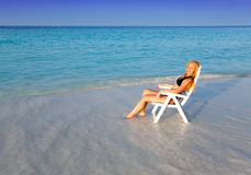 Young pretty woman tans in beach chair.Portrait in a sunny day Stock Photos