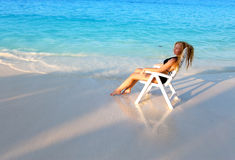 Young pretty woman tans in beach chair, it put in ocean Stock Photography