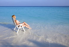 Young pretty woman tans in beach chair in sea Stock Image