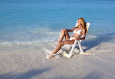 Young pretty woman tans in beach chair in sea Stock Photo