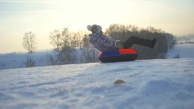 Young pretty woman tobogganing in the mountain through the sun in slow motion during beautiful sunset. 1920x1080 stock video footage