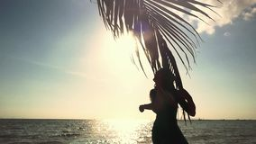 Young pretty woman touching palm leaf on the sun and the sea background. Girl poses on camera in slow motion with lens stock video