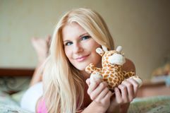 Young pretty woman with a toy on the bed Royalty Free Stock Image