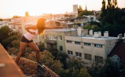 Young pretty woman training martial arts on rooftop Stock Images