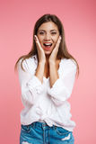 Young pretty woman in tredny outfit looks happy and surprised Royalty Free Stock Image