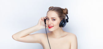 Young pretty woman trendy makeup bright red lips bun hairstyle bare shoulders act the ape with big dj headphones on white studio b. Young pretty llllady trendy Stock Photo