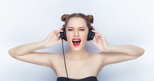 Young pretty woman trendy makeup bright red lips bun hairstyle bare shoulders act the ape with big dj headphones on white studio b Royalty Free Stock Image
