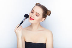 Young pretty woman trendy makeup bright red lips bun hairstyle bare shoulders act the ape with brush white studio background Royalty Free Stock Images