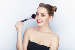 Young pretty woman trendy makeup bright red lips bun hairstyle bare shoulders act the ape with brush white studio background Stock Image