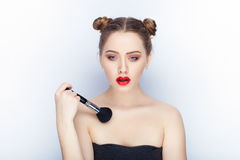 Young pretty woman trendy makeup bright red lips bun hairstyle bare shoulders act the ape with brush white studio background Stock Photography