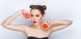 Young pretty woman trendy makeup bright red lips bun hairstyle bare shoulders act the ape with grapefruits white studio background Stock Photo
