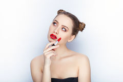Young pretty woman trendy makeup bright red lips bun hairstyle bare shoulders act the ape with lipstick white studio background Royalty Free Stock Images
