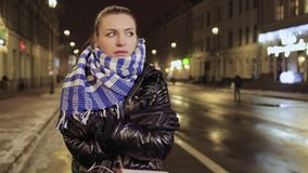 Young girl feels herself cold during waiting friends at the urban street. Young pretty woman tries to warm up herself. The woman is frozen and blows warm air on stock video footage