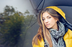 Young pretty woman with umbrella wearing warm yellow coat Royalty Free Stock Image