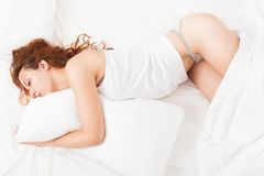 Young pretty woman in underwear sleeping on white pillow in bed Royalty Free Stock Images
