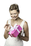 Young pretty woman unwraps gift stock photography