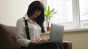 Young woman using laptop at home sitting on sofa. Young pretty woman using laptop. Smiling girl sitting on sofa relaxing while browsing online shopping website stock video footage