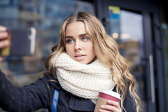 Young and pretty woman using phone holding a cup of coffee in the dark cafe Royalty Free Stock Images