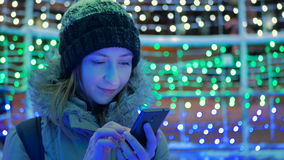 Young pretty woman using smartphone in the city at night. Christmas, technology and holiday concept stock footage