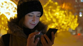 Young pretty woman using smartphone in the city at night. Christmas, winter, technology and holiday concept stock video