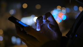 Young pretty woman using smartphone in the city at night. Close-up shot of woman hands with smartphone in the city at night. Technology, winter and holiday stock video