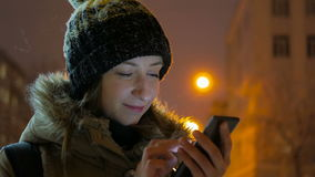 Young pretty woman using smartphone in the city at night. Technology, winter and holiday concept stock footage