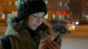 Young pretty woman using smartphone in the city at night stock video footage